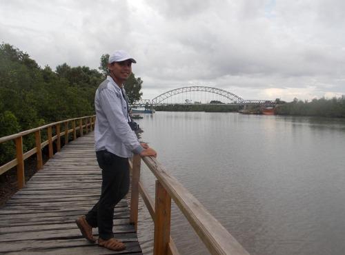 Berfoto dengan latar belakang jembatan sei carang
